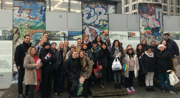 Group of students smiling in front of the Berlin wall