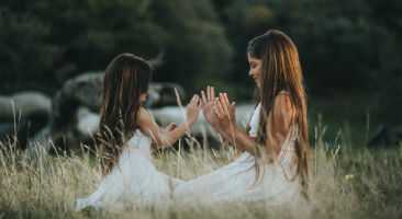 Two girls clapping hands together in a field