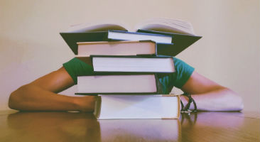 Student hidden behind stack of books