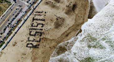 Aerial view of people forming word 'Resist!!' on beach