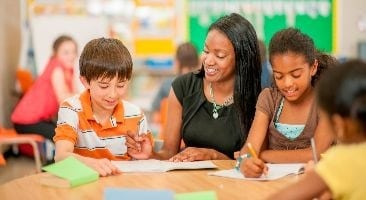 Female teacher teaching two young students